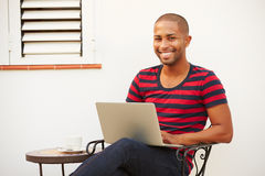 Young Man Sitting Outdoors With Laptop And Drinking Coffee Royalty Free Stock Image