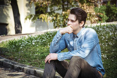Young man sitting outdoors in public park Royalty Free Stock Photo