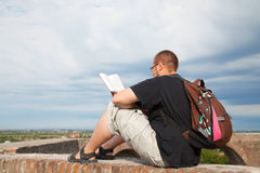 Young man sitting outdoors reading Stock Image
