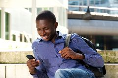Young man sitting outdoors and using mobile phone. Portrait of young man sitting outdoors on steps and reading text message on his mobile phone royalty free stock images