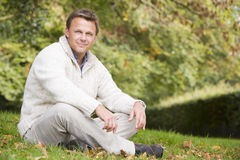 Young man sitting outside in autumn landscape Stock Photo