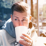 Young man sitting outside and drinking coffee Stock Image