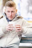 Young man sitting outside and drinking coffee Stock Images