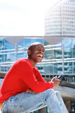 Young man sitting outside with mobile phone and laughing. Portrait of young african man sitting outside in the city with mobile phone and laughing Stock Image