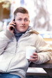 Young man sitting outside and talking on the phone Stock Photo