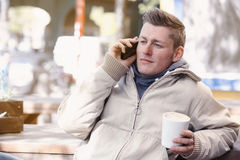 Young man sitting outside and talking on the phone Royalty Free Stock Images
