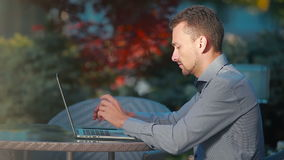 Young man sitting outside and working with laptop stock footage