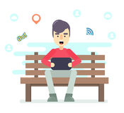 Young man sitting in the park on the bench with tablet in hands Royalty Free Stock Photography
