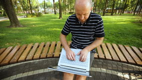 Young Man Sitting On Park Bench Using Laptop In Sunny Day stock footage