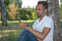 Young man sitting in the park with cell phone Stock Images