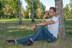 Young man sitting in the park with cell phone Royalty Free Stock Image