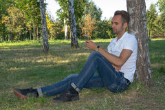 Young man sitting in the park with cell phone Stock Image