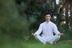 Young man sitting in the park doing meditation Stock Image