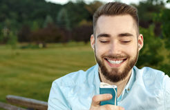 Young man sitting in the park listens to music. While sitting on the bench Stock Photos