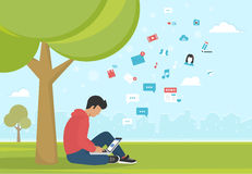 Young man sitting in the park under a tree and working with laptop Royalty Free Stock Photos