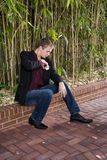 Young man sitting on patio fixing handkerchief. Young well-dressed man sitting on patio fixing handkerchief Royalty Free Stock Photography