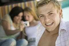 Young man sitting on patio smiling Royalty Free Stock Images