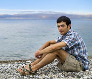 Young man sitting on pebble beach during sunset Stock Photos