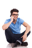 Young man sitting while on the phone Stock Image