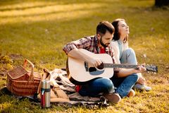 Young man sitting on picnic blanket with his girlfriend. Young men sitting on picnic blanket with his girlfriend and playing guitar royalty free stock photos