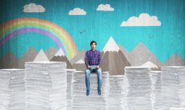 Young man sitting on pile of paper documents. Attractive man in casual clothing sitting on pile of documents with sketched landscape view on background. Mixed Stock Image