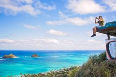 Young man sitting on pillbox over looking Lanikai taking a cell. After reaching his final destination a young man sits on pillbox over looking Lanikai taking a Royalty Free Stock Photo