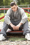 Young Man Sitting In Playground stock images