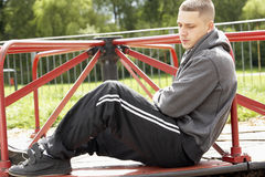 Young Man Sitting In Playground. Close up of Young Man Sitting In Playground royalty free stock image