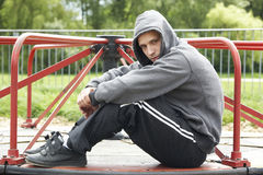 Young Man Sitting In Playground Stock Image