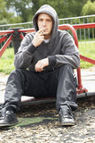 Young Man Sitting In Playground Smoking Joint Royalty Free Stock Photography