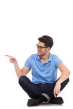 Young man sitting and pointing sideways Stock Photo
