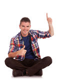 Young man sitting and pointing up Royalty Free Stock Photo