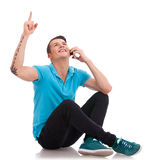 Young man sitting, pointing up Stock Photos