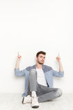Young man sitting and pointing upwards with hands Royalty Free Stock Photography
