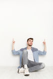 Young man sitting and pointing upwards with hands Stock Photo