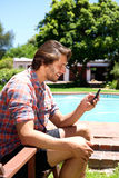 Young man sitting by pool holding cellphone Stock Photo