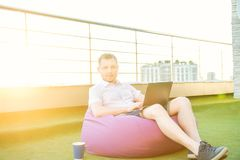 Young man sitting on pouf on green lawn of office balcony with cityscape background, working on laptop. Back sunset light. Mobile Stock Photo