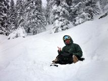 Young man sitting from powder snow. Riding with snowboard from powder snow hill or mountain Stock Photography