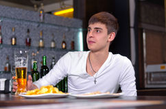 Young man sitting in the pub with a beer Stock Photos