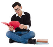 Young man sitting  and reading  book Royalty Free Stock Photography