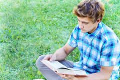 Young man is sitting and reading a book Stock Photo