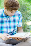 Young man is sitting and reading a book Royalty Free Stock Image