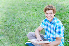 Young man is sitting and reading a book Stock Image