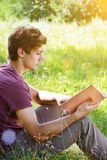 Young man is sitting and reading a book Royalty Free Stock Images