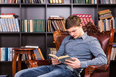 Young man sitting reading in the library. Handsome young man sitting reading in a brown leather armchair the library concentrating on his book Royalty Free Stock Photography