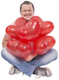 Young man sitting with red balloons on white Stock Images