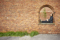 Young man sitting on red brick wall window royalty free stock photos
