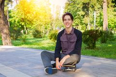 Young man sitting and relaxing on skateboard after skating in city park. Teen boy skater. Young man sitting and relaxing on skateboard after skating in city royalty free stock images