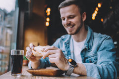 Young man sitting in a restaurant and eating a hamburger Royalty Free Stock Image