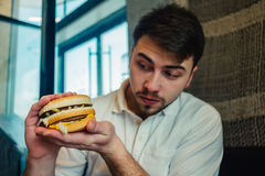 A young man sitting in a restaurant and holding a meat burger. Man is eating in a restaurant and enjoying delicious food Stock Image
